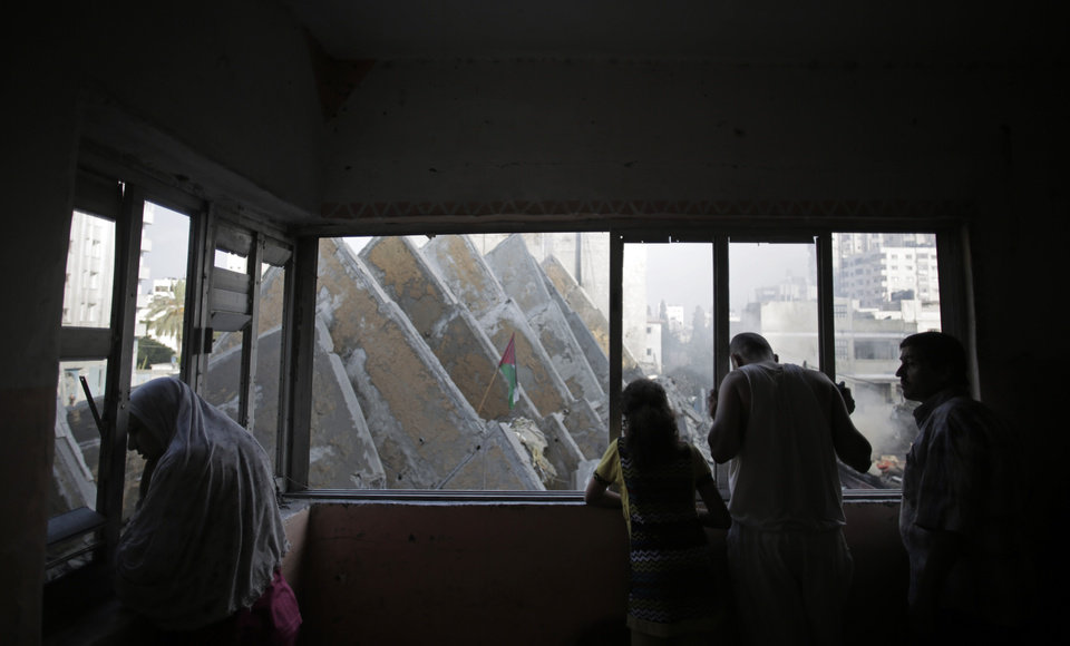Photo - A Palestinian family watch from a window as people below inspect the rubble of the 15-story Basha Tower that collapsed following early morning Israeli airstrikes, in Gaza City, Tuesday, Aug. 26, 2014. Tuesday's strikes leveled the Basha Tower with apartments and offices and severely damaged another high-rise, the Italian Complex, built in the 1990s by an Italian businessman, with dozens of shops and offices. Both buildings were evacuated after receiving warnings of impending strikes. (AP Photo/Khalil Hamra)