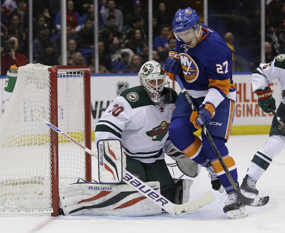 Photo - Minnesota Wild goalie Ilya Bryzgalov, left defends the goal while New York Islanders' Anders Lee skates past during the second period of the NHL hockey game, Tuesday, March 18, 2014, in Uniondale, New York. (AP Photo/Seth Wenig)