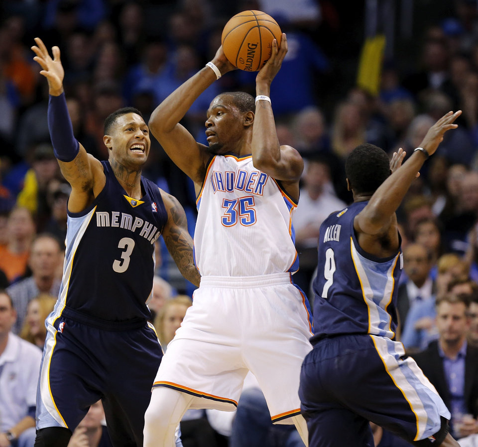 Photo - Oklahoma City's Kevin Durant (35) passes away from Memphis' James Johnson (3) and Tony Allen (9) during an NBA basketball game between the Memphis Grizzlies and the Oklahoma City Thunder at Chesapeake Energy Arena in Oklahoma City, Friday, Feb. 28, 2014. Oklahoma City won, 113-107. Photo by Nate Billings, The Oklahoman