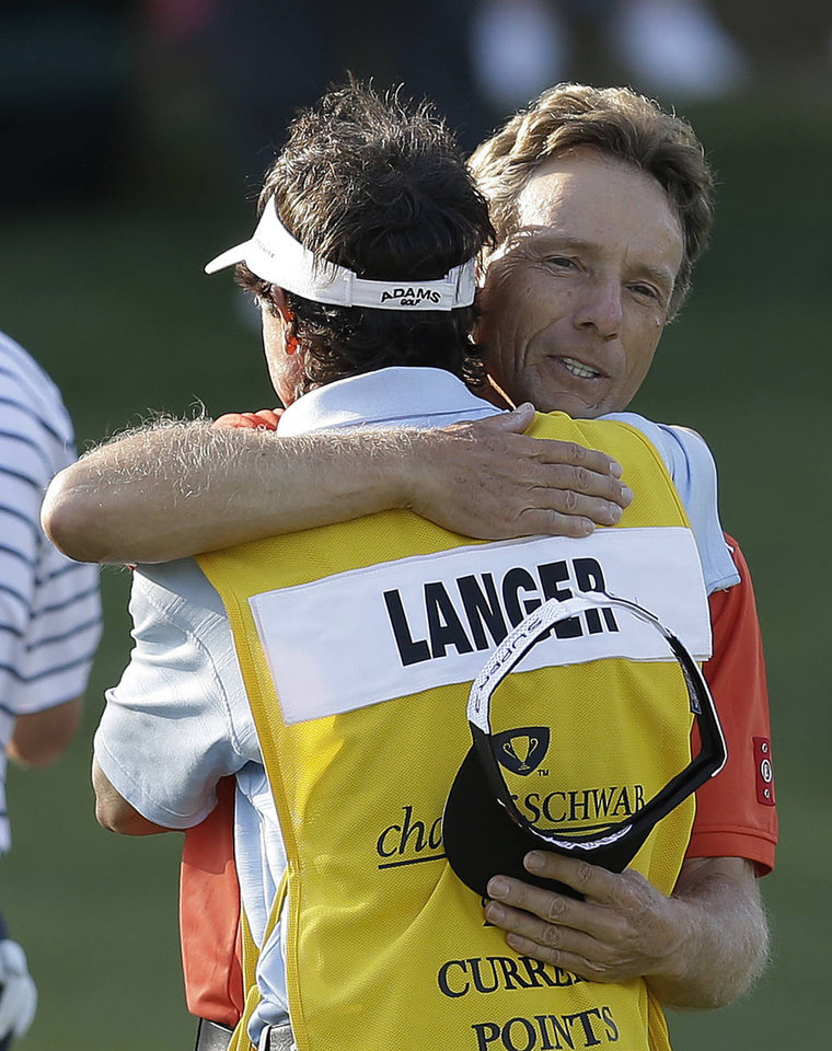 Photo - Bernhard Langer, right, of Germany, hugs his caddie after winning the Greater Gwinnett Championship golf tournament on Sunday, April 21, 2013, in Duluth, Ga. (AP Photo/John Bazemore)