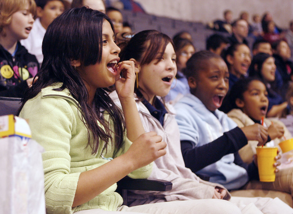 Photo - Maximina Mendez, 12, (left), Cheyenne Tijerina, 11, and Ayana Tillman, 11, from Parmelee School, cheer for the Blazers as schoolchildren from across the metro attend a hockey game, with OKC playing against Texas at the Ford Center in Oklahoma City, OK, Tuesday, Feb. 10, 2009. BY PAUL HELLSTERN, THE OKLAHOMAN