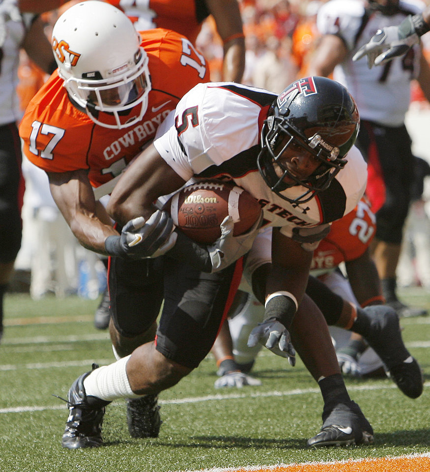 Photo - Texas Tech's Michael Crabtree (5) makes his way past Oklahoma State's Jacob Lacey (17) for a touchdown during the first half of the college football game between the Oklahoma State University Cowboys (OSU) and the Texas Tech University Red Raiders (TTU) at Boone Pickens Stadium in Stillwater, Okla., on Saturday, Sept. 22, 2007.  By NATE BILLINGS, The Oklahoman  ORG XMIT: KOD