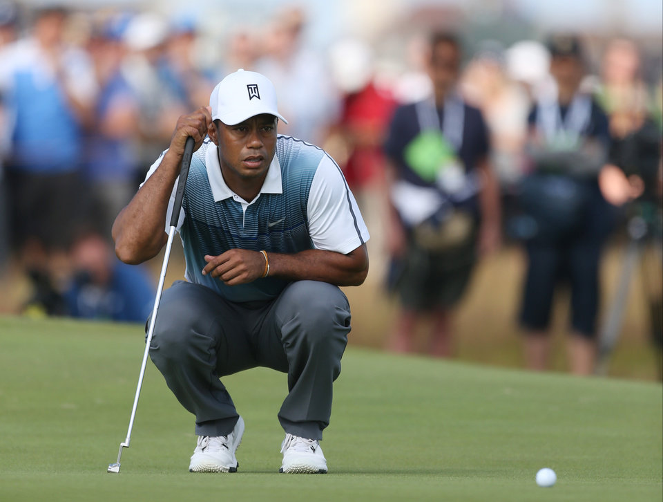 Photo - Tiger Woods of the US looks at his putt on the 2nd green during the first day of the British Open Golf championship at the Royal Liverpool golf club, Hoylake, England, Thursday July 17, 2014. (AP Photo/Peter Morrison)