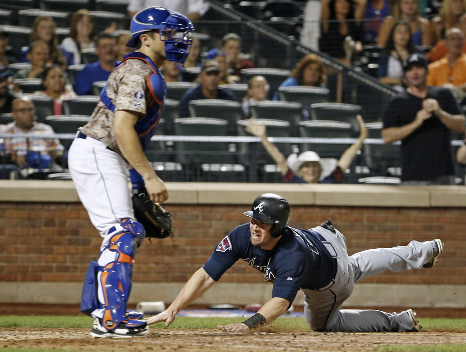 Photo - New York Mets catcher Travis d'Arnaud watches without a ball to make the tag as Atlanta Braves Chris Johnson, right, dives into the plate to score on Christian Bethancourt's eighth-inning, softly-hit RBI single in a baseball game in New York, Monday, July 7, 2014. (AP Photo/Kathy Willens)