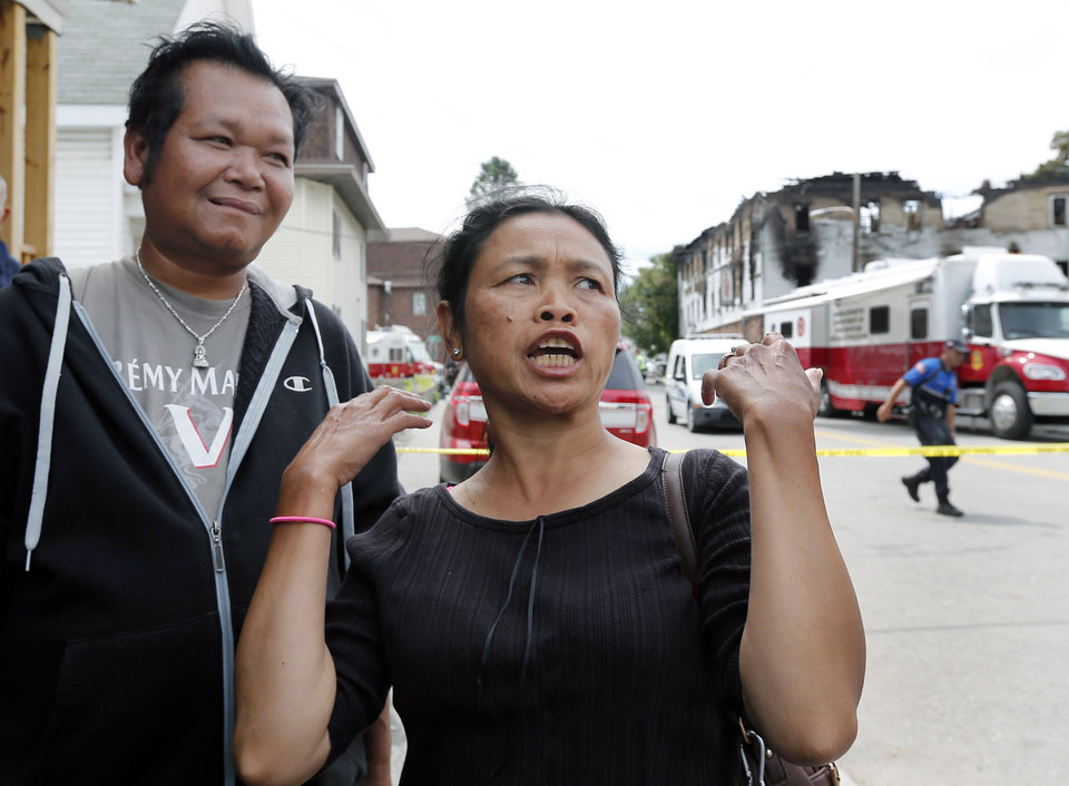 Photo - Tha Doss speaks across from a burned three-story apartment and business building in Lowell, Mass., Thursday, July 10, 2014, where she said her boyfriend Odum Chaloeurn, left, helped her escape from the burning apartment. Officials said four adults and three children died in the fast-moving pre-dawn fire. The cause and origin of the blaze remain under investigation, State Fire Marshal Stephen Coan said.  (AP Photo/Elise Amendola)