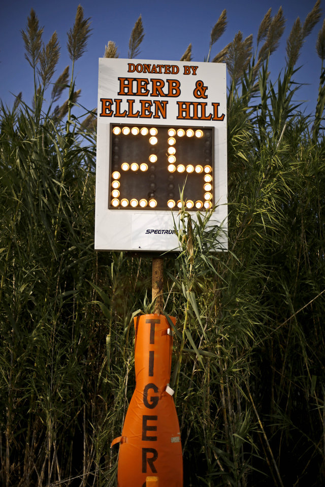 Photo - Plants grow around the play clock for the high school football game between Cashion and Crescent in Crescent, Okla., Thursday, Oct. 18, 2012. Photo by Bryan Terry, The Oklahoman