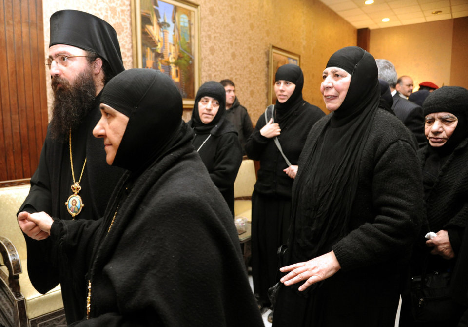 Photo - In this photo released by the Syrian official news agency SANA, a group of nuns who were freed after being held by rebels, greet church officials at the Syrian border town of Jdeidat Yabous, early Monday, March. 10, 2014. Rebels in Syria freed more than a dozen Greek Orthodox nuns on Monday, ending their three-month captivity in exchange for Syrian authorities releasing dozens of female prisoners. The release of the nuns and their helpers, 16 women in all, is a rare successful prisoner-exchange deal between Syrian government authorities and the rebels seeking to overthrow the rule of President Bashar Assad. (AP Photo/SANA)