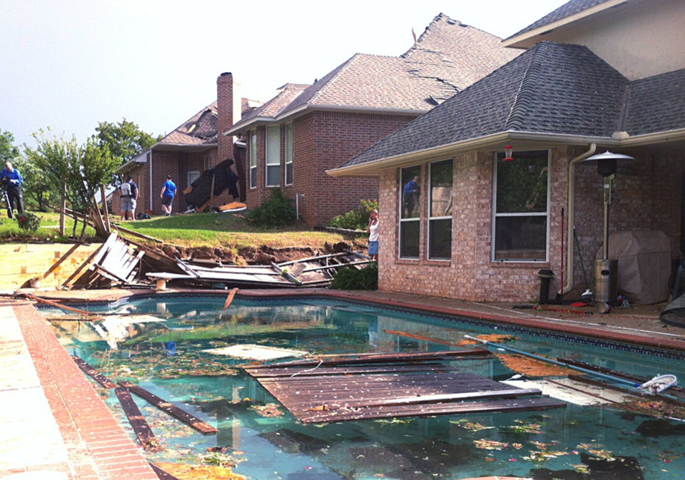 Photo - People survey damage from a tornado that hit Edmond, Okla., on Sunday, May 19, 2013. A powerful storm system rumbled through the Plains and upper Midwest on Sunday, spawning tornadoes that damaged roofs and structures near Oklahoma City and kicked up debris in Wichita, Kan. (AP Photo/Sean Murphy)