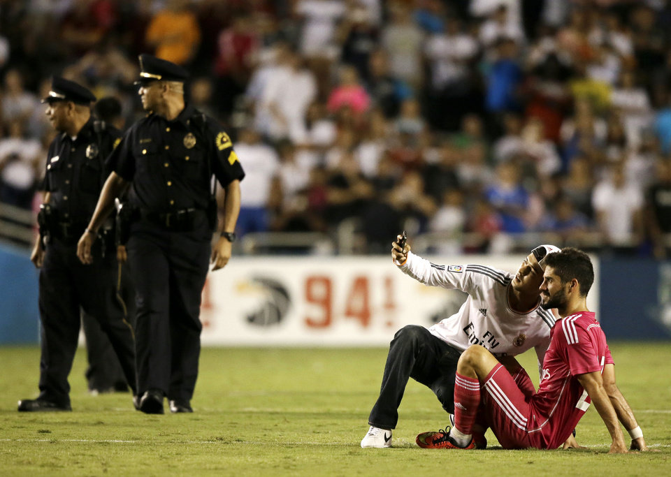 Photo - Police officers walk over to remove a fan that made it onto the field and proceeded to take a selfie with Real Madrid's Isco, right, in the second half of a Guinness International Champions Cup soccer tournament match against Roma, Tuesday, July 29, 2014, in Dallas. Several fans made it onto the field, some able to acquire autographs from players, in the final minutes of the 1-0 Roma win. (AP Photo/Tony Gutierrez)