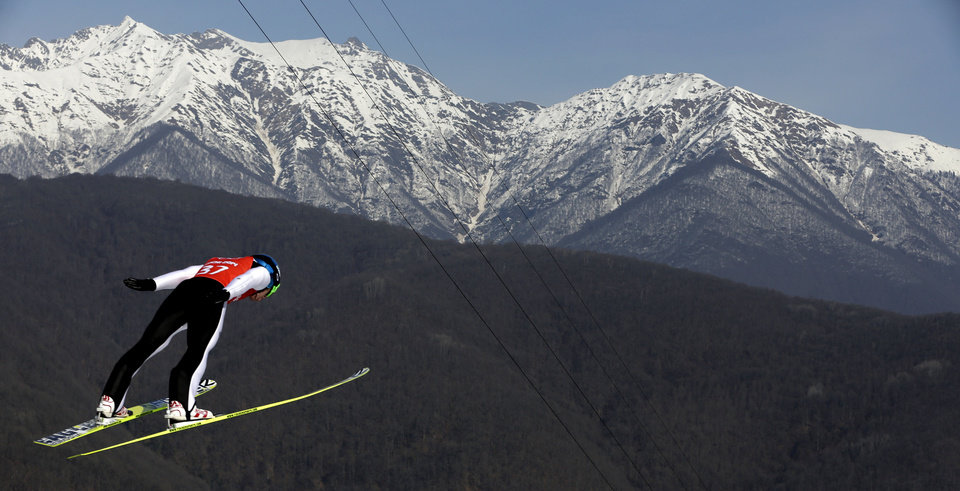 Photo - Alessandro Pittin soars through the air during a Nordic Combined training at the 2014 Winter Olympics, Sunday, Feb. 16, 2014, in Krasnaya Polyana, Russia. (AP Photo/Matthias Schrader)
