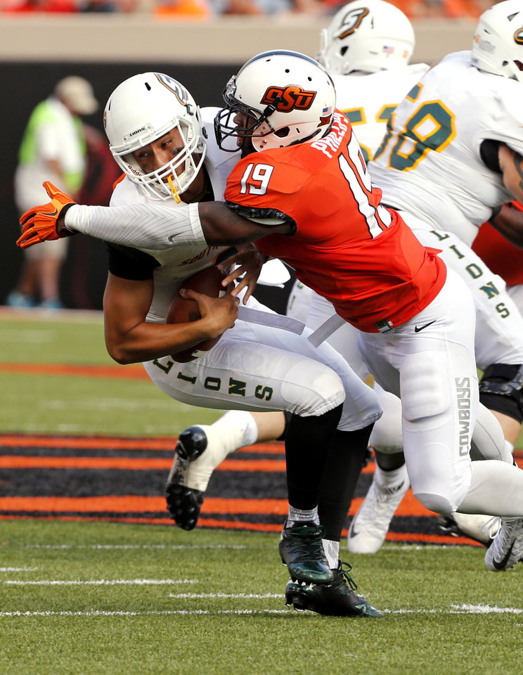 Photo - Oklahoma State's Justin Phillips (19) sacks quarterback Justin Alo (8) during the second half of a college football game between the Oklahoma State Cowboys (OSU) and the Southeastern Louisiana Lions at Boone Pickens Stadium in Stillwater, Okla., Saturday, Sept. 12, 2015. Photo by Steve Sisney, The Oklahoman