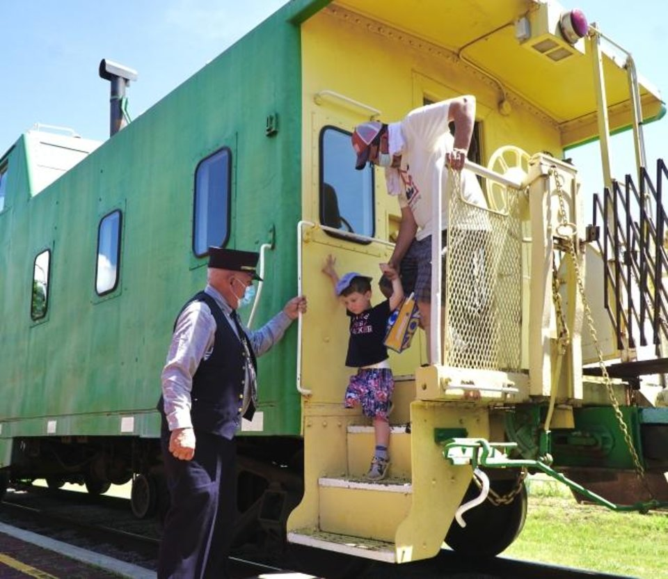 Photo -  Oklahoma Railway Museum conductor Steve Davis helps Shephard Edwards and his father Scott climb down from a caboose after a train ride Saturday.  [JORDAN GREEN PHOTOS/THE OKLAHOMAN]