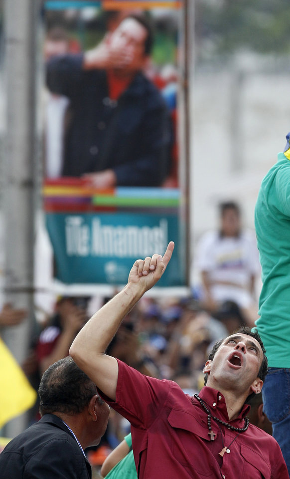 Backdropped by a poster showing late President Hugo Chavez, opposition presidential candidate Henrique Capriles cheers during a campaign rally at Bolivar Avenue in Caracas, Venezuela, Sunday, April 7, 2013. Capriles is running against ruling party candidate Nicolas Maduro in next weekend's presidential election.(AP Photo/Ariana Cubillos)