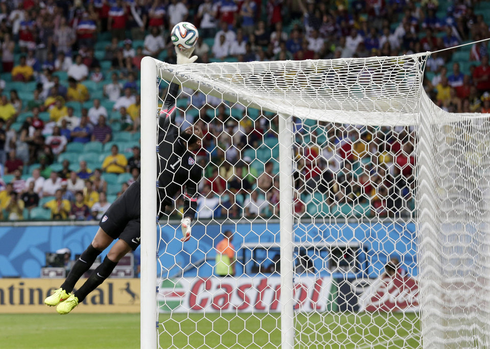 Photo - United States' goalkeeper Tim Howard leaps to make a save during the World Cup round of 16 soccer match between Belgium and the USA at the Arena Fonte Nova in Salvador, Brazil, Tuesday, July 1, 2014. (AP Photo/Marcio Jose Sanchez)