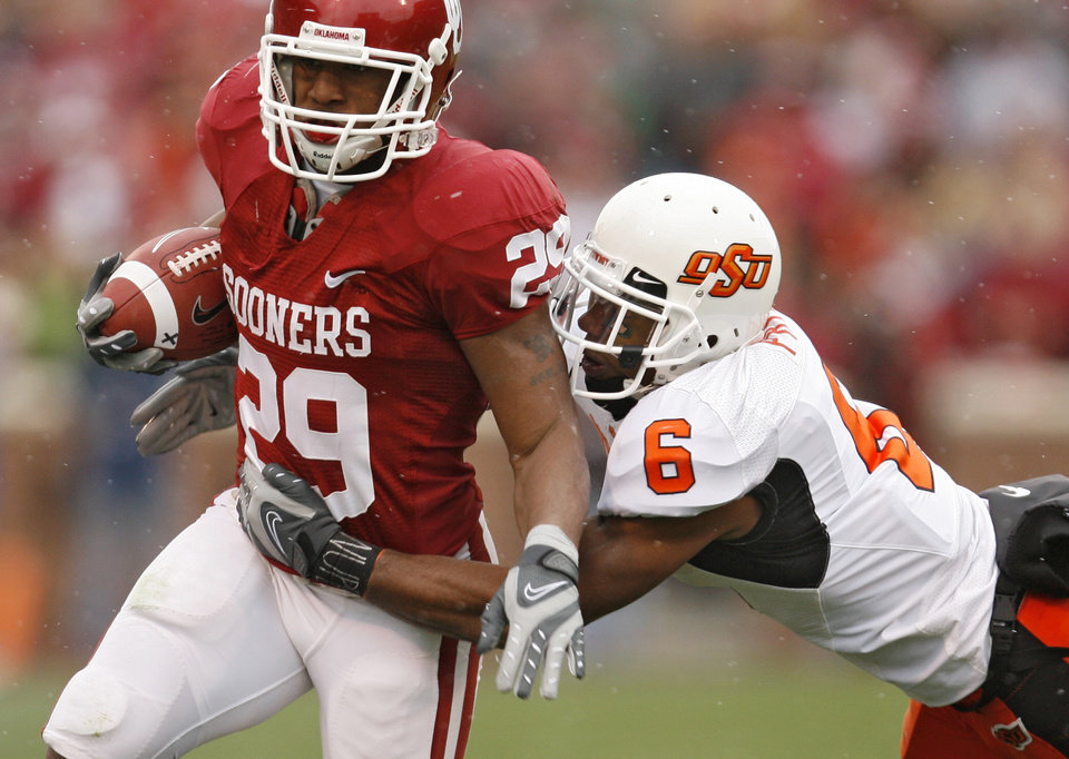 Photo - Oklahoma's Chris Brown (29) looks for running room past Oklahoma State's Ricky Price (6) during the first half of the college football game between the University of Oklahoma Sooners (OU) and the Oklahoma State University Cowboys (OSU) at the Gaylord Family-Memorial Stadium on Saturday, Nov. 24, 2007, in Norman, Okla.  Photo By Bryan Terry, The Oklahoman