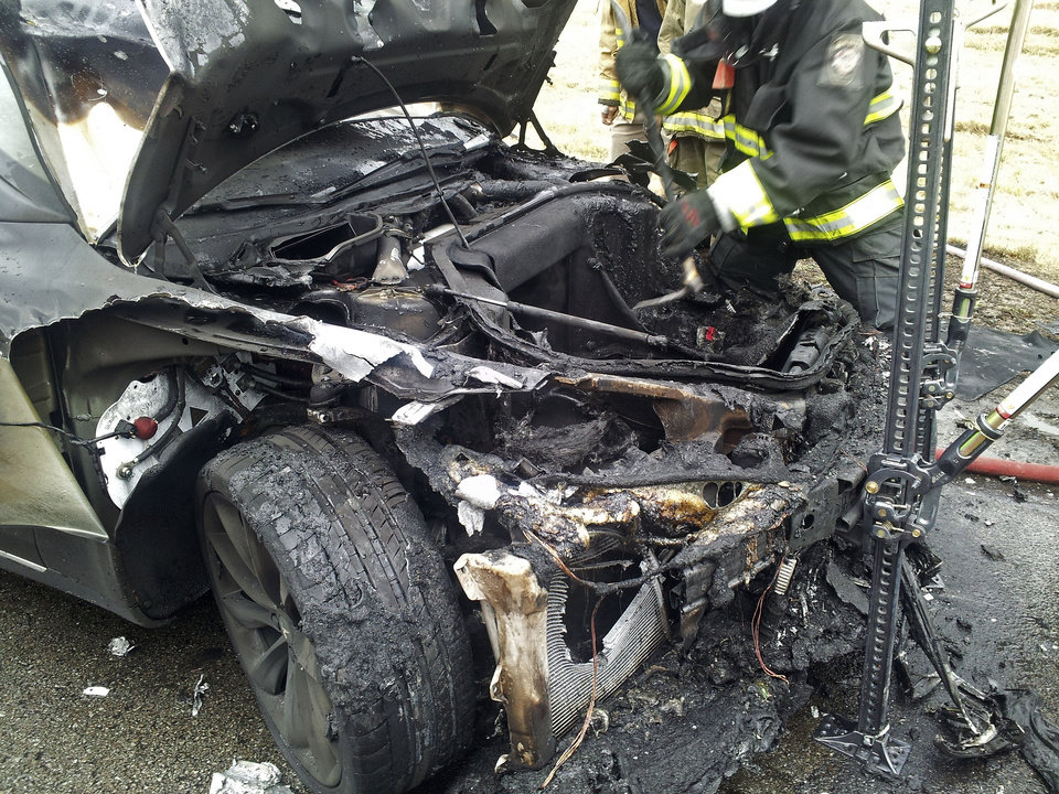 Photo - In this Wednesday, Nov. 6, 2013 photo provided by the Tennessee Highway Patrol, emergency workers respond to a fire on a Tesla Model S electric car in Smyrna, Tenn. Spokeswoman Liz Jarvis Shean says Tesla has sent a team to Tennessee to investigate the fire. Two other Model S cars have caught fire in the past five weeks, one near Seattle and the other in Mexico. (AP Photo/Tennessee Highway Patrol)