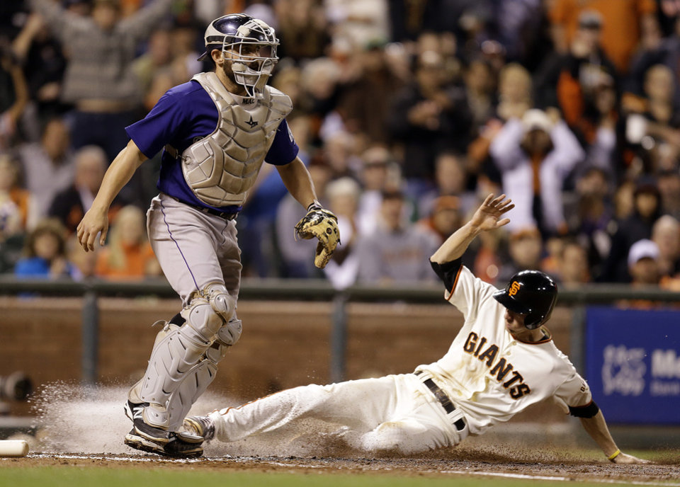 Photo - San Francisco Giants' Matt Duffy, right, slides to score past Colorado Rockies catcher Michael McKenry in the fourth inning of a baseball game Wednesday, Aug. 27, 2014, in San Francisco. Duffy scored on a bunt by Gregor Blanco. (AP Photo/Ben Margot)