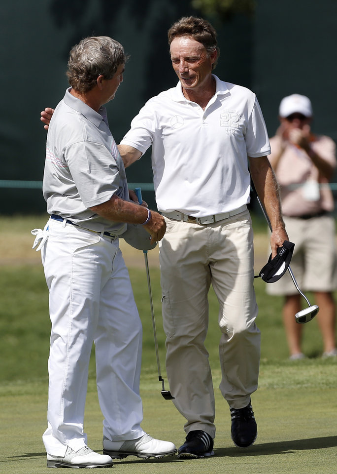 Photo - Gene Sauers, left, and Bernhard Langer shake hands on the 18th hole in the third round of the U.S. Senior Open golf tournament at Oak Tree National in Edmond, Okla., Saturday, July 12, 2014. Photo by Sarah Phipps, The Oklahoman