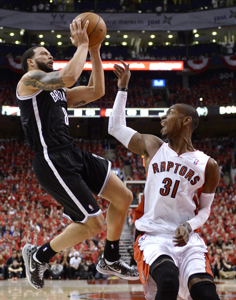 Photo - Brooklyn Nets' Deron Williams, left, drives to the net against Toronto Raptors' Terrence Ross during the second half of Game 7 of the opening-round NBA basketball playoff series in Toronto, Sunday, May 4, 2014. (AP Photo/The Canadian Press, Frank Gunn)