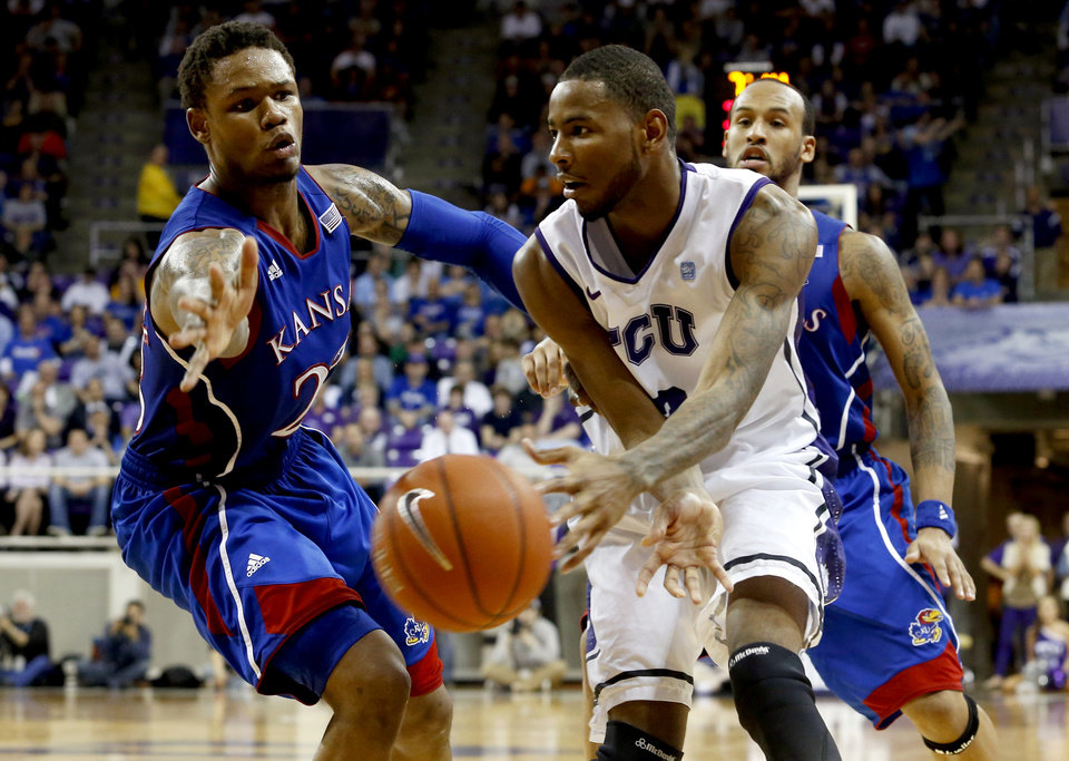 Photo - Kansas guard Ben McLemore, left, defends as TCU forward Connell Crossland passes the ball during the second half of an NCAA college basketball game, Wednesday, Feb. 6, 2013, in Fort Worth, Texas. TCU won 62-55. (AP Photo/Sharon Ellman)