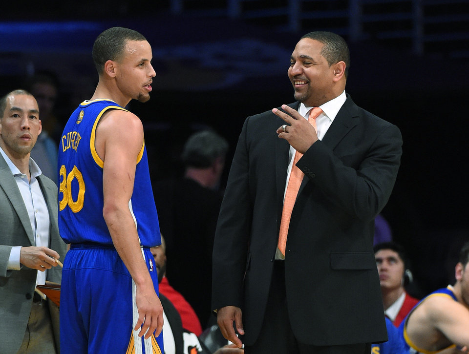 Photo - Golden State Warriors guard Stephen Curry, left, talks with coach Mark Jackson after achieving a triple-double, during the second half of an NBA basketball game against the Los Angeles Lakers, Friday, April 11, 2014, in Los Angeles. The Warriors won 112-95. (AP Photo/Mark J. Terrill)