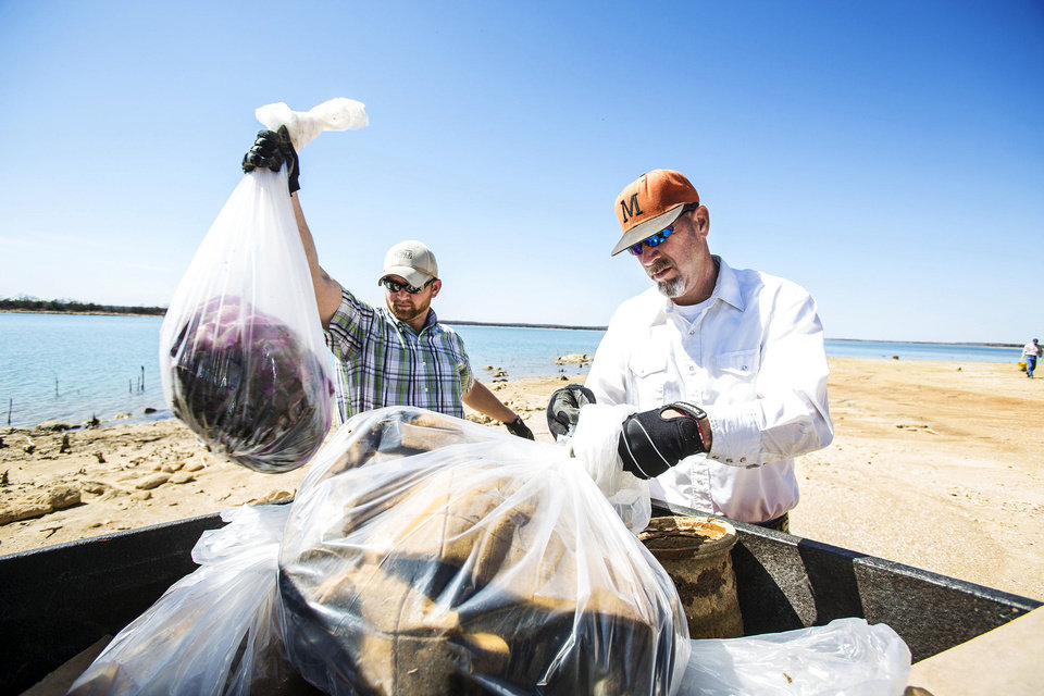 Photo - Brian Williams, left, and Kevin Lynch, both agricultural research assistants with the Noble Foundation, load trash collected from the shore of Lake Murray. The Noble Foundation Employee Team participates in the annual lake clean up as part of the foundation's Noble in the Community program.  Photo Provided - Photo provided