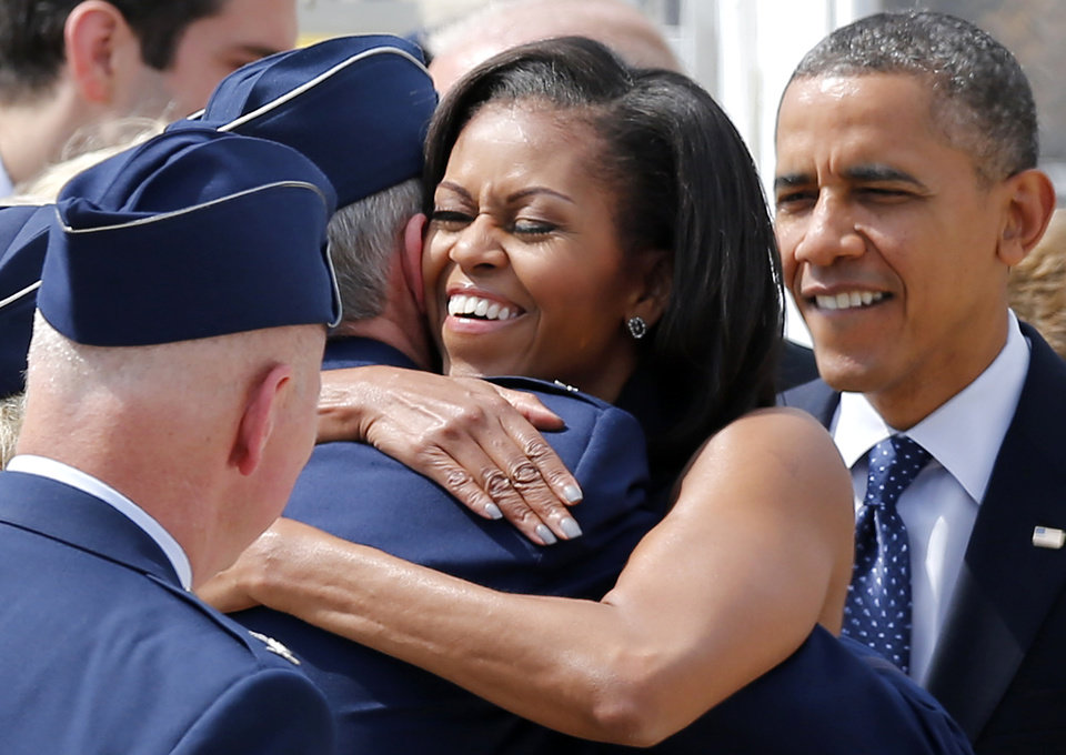 Photo -   President Barack Obama watches as his wife, first lady Michelle Obama, greets service members upon their arrival at Pease Air National Guard Base in Portsmouth, N.H., Friday, Sept. 7, 2012. (AP Photo/Winslow Townson)