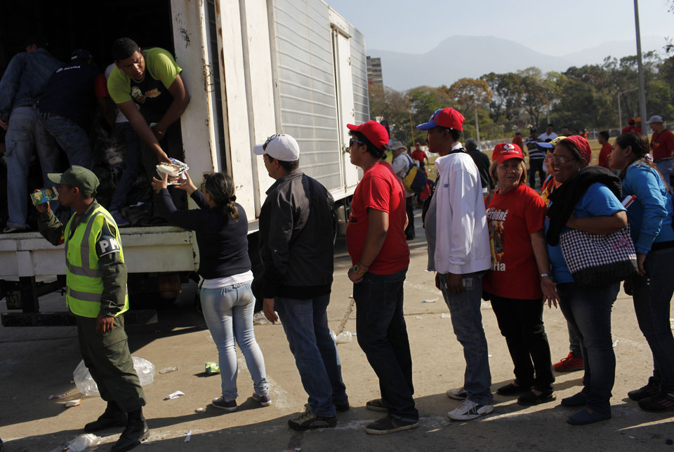People line up for lunch boxes being distributed outside the military academy where a funeral ceremony will take place for Venezuela's late President Hugo Chavez in Caracas, Venezuela, Friday, March 8, 2013. Friday's funeral promises to be a final turn on the world stage for Chavez after 14 years in power, though in some ways the former paratrooper is not going anywhere: Venezuela announced Thursday that it would embalm his body and put it on permanent display. Chavez died on March 5 after a nearly two-year bout with cancer.  He was 58. (AP Photo/Rodrigo Abd)