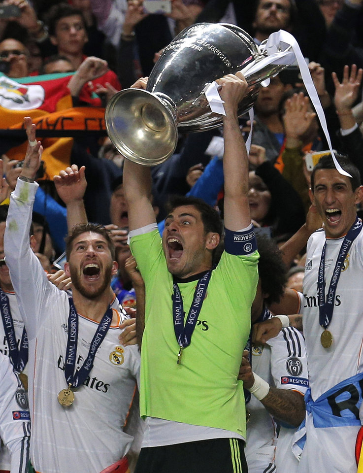 Photo - Real goalkeeper Iker Casillas, centre, lifts the Champion League trophy, at the end of the Champions League final soccer match between Atletico Madrid and Real Madrid, at the Luz stadium, in Lisbon, Portugal, Saturday, May 24, 2014. (AP Photo/Daniel Ochoa de Olza)