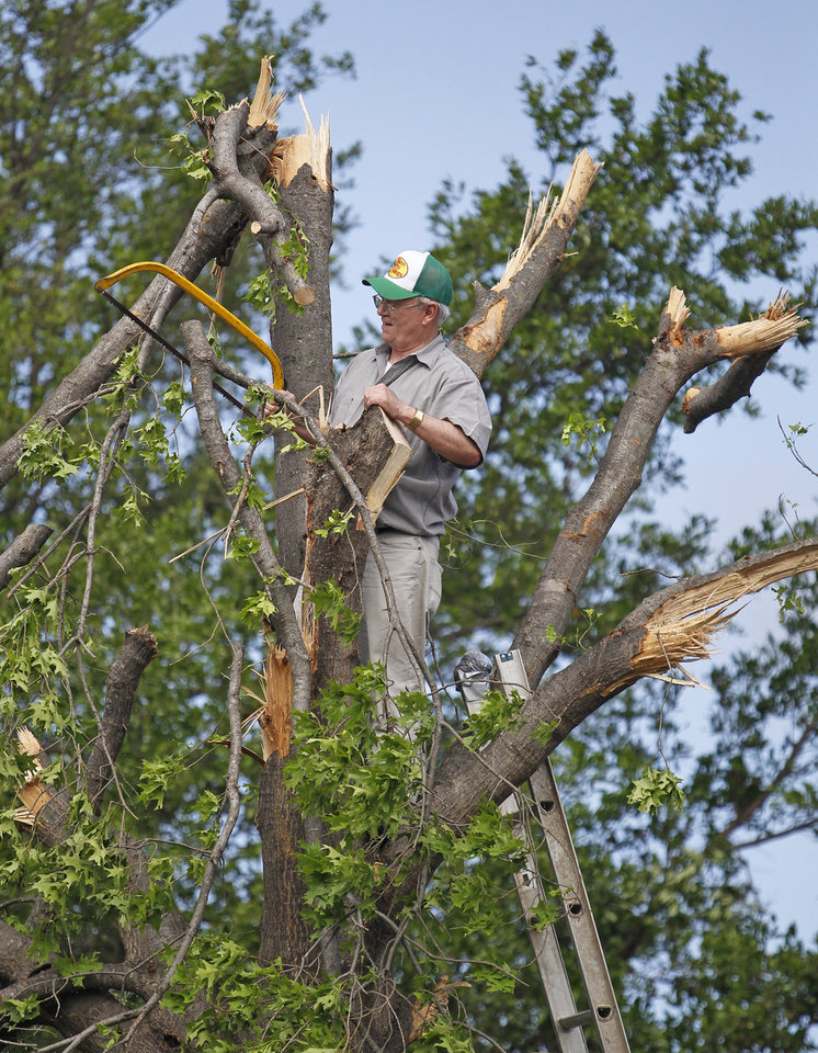 Homeowner Jim Pinker climbs  to the top of his damaged tree to begin the pruning after a severe storm passed the area, Wednesday, April 4, 2012 in Arlington, Texas. Preliminary findings indicate one of the tornadoes that struck North Texas had wind gusts ranging from 136 to 165 mph.  As many as a dozen twisters touched down across Dallas-Fort Worth. Thousands remained without power Wednesday and hundreds of homes were severely damaged.  Officials reported more than 20 injuries, but no deaths. (AP Photo/The Fort Worth Star-Telegram, Paul Moseley)  MANDATORY CREDIT ORG XMIT: TXFOR110