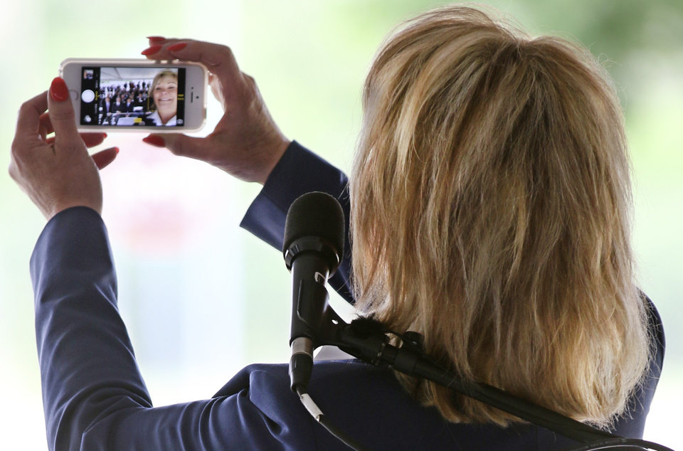 Photo -  Gov. Mary Fallin takes a picture to send to Texas Gov. Rick Perry during a groundbreaking ceremony for the new GE Global Research Center. Photo by Steve Gooch, The Oklahoman   Steve Gooch -  The Oklahoman