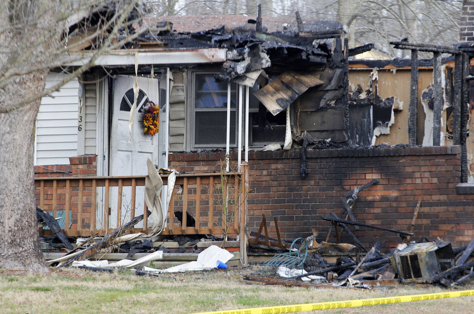 This Sunday, March 10, 2013 photo shows the charred remains of a home after a fire erupted, Saturday, March 9, 2013 in Gray, Ky, killing two adults and five children inside. (AP Photo/Lisa Norman-Hudson)