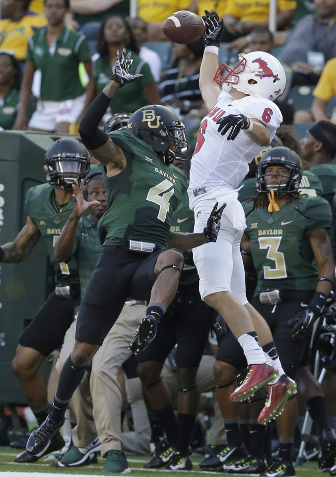 Photo - SMU wide receiver Stephen Nelson (6) can't catch the pass against Baylor cornerback Xavien Howard (4) during the first half of an NCAA college football game Sunday, Aug. 31, 2014, in Waco, Texas. (AP Photo/LM Otero)
