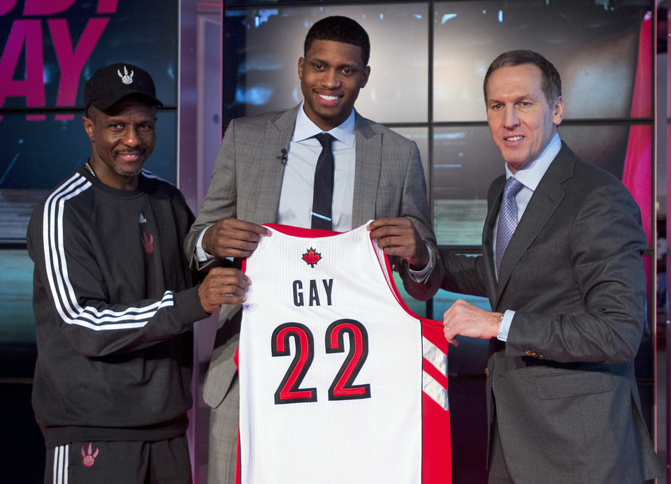 Toronto Raptors newly-acquired forward Rudy Gay, center, pose for a photograph with  Raptors president and general manager Bryan Colangelo, right, and head coach Dwane Casey, left, during an NBA basketball press conference in Toronto on Friday, Feb. 1, 2013. (AP Photo/The Canadian Press, Nathan Denette)