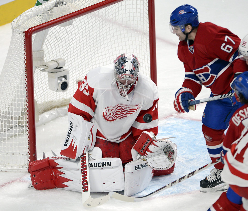 Photo - Detroit Red Wings goalie Jimmy Howard (35) stops a shot in front of Montreal Canadiens left wing Max Pacioretty (67) during the first period of an NHL hockey game Wednesday, Feb. 26, 2014, in Montreal. (AP Photo/The Canadian Press, Ryan Remiorz)