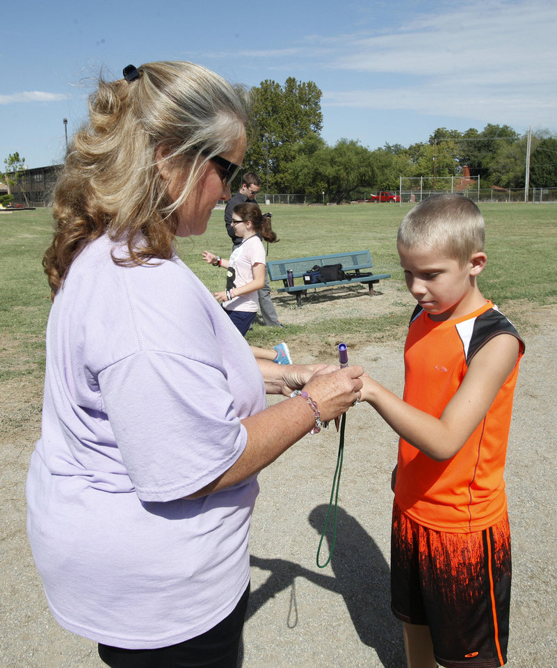 Physical education teacher Angela Stogsdill marks a completed lap for fifth-grader Wyatt Pitt.