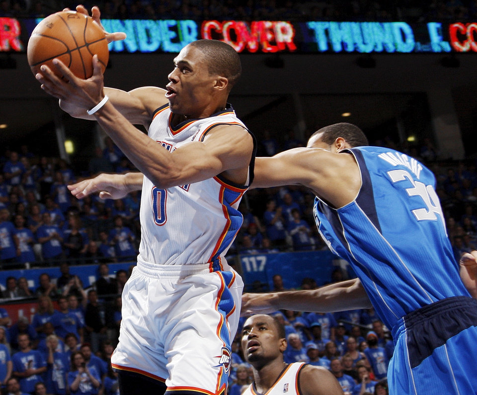 Photo - Oklahoma City's Russell Westbrook (0) takes the ball to the hoop as he's fouled by Dallas' Brendan Wright (34) in the fourth quarter during game one of the first round in the NBA playoffs between the Oklahoma City Thunder and the Dallas Mavericks at Chesapeake Energy Arena in Oklahoma City, Saturday, April 28, 2012. Westbrook made the lay-up and the foul shot. Oklahoma City won, 99-98. Photo by Nate Billings, The Oklahoman
