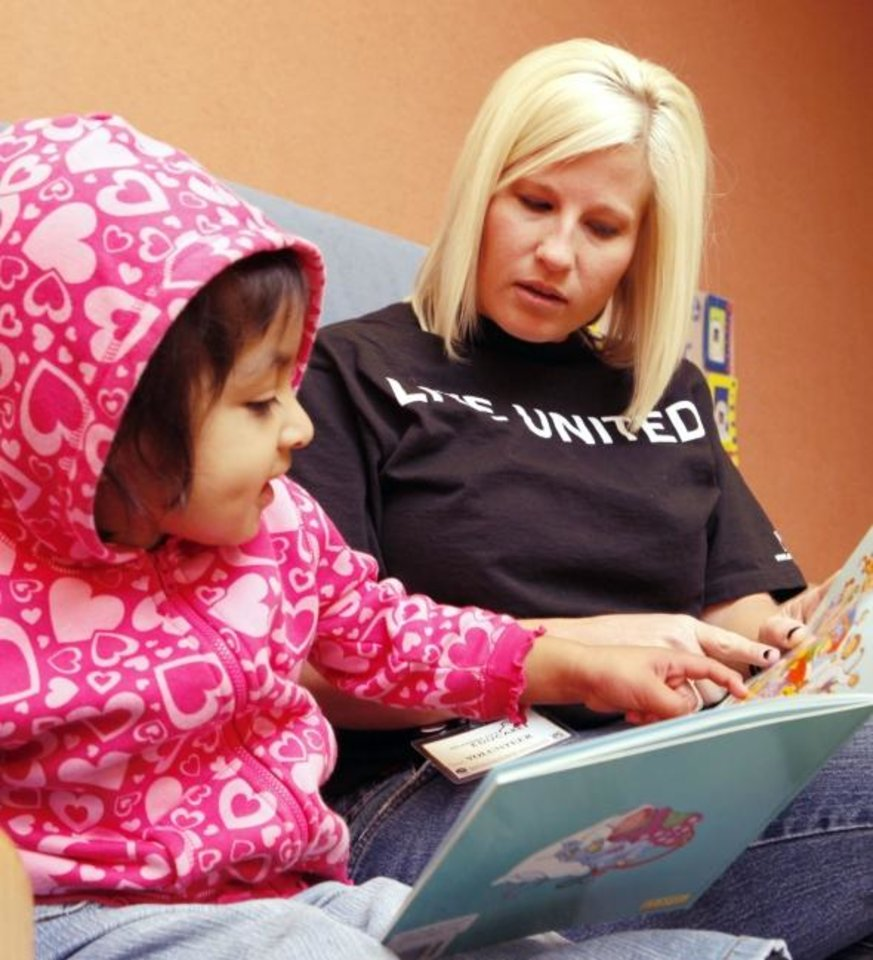 Photo - Shannon Bernstein reads to two year old Adriana Hernandez, as volunteers with Enterprise Holdings assist teachers in classrooms and spend time with the children at Sunbeam Family Services' Educare in Oklahoma City, OK, Friday, Oct. 8, 2010. By Paul Hellstern, The Oklahoman ORG XMIT: KOD
