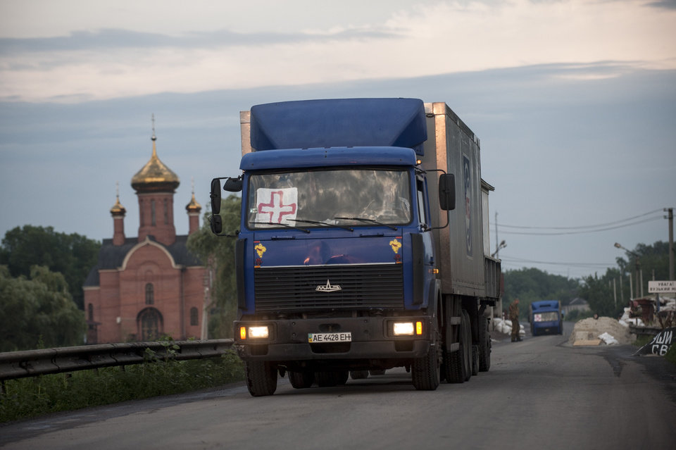 Photo - Trucks carrying the bodies of Ukrainian troops killed in a plane shot down near Luhansk, cross over to the Ukrainian side during a handover by pro-Russian fighters at a check point in the village of Karlivka near Donetsk, eastern Ukraine, Wednesday, June 18, 2014. The two sides managed to arrange a brief truce Wednesday evening in the eastern town of Karlivka to allow pro-Russian forces to hand over the bodies of 49 Ukrainian troops who died when the separatists shot down a transport plane bound for the airport in Luhansk last weekend.  (AP Photo/Evgeniy Maloletka)