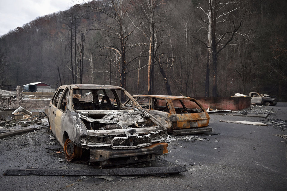 Photo - Burnt vehicles remain among the damage from wildfires at Creek Place Efficiencies in Gatlinburg, Tenn., Wednesday, Nov. 30, 2016. Tornadoes that dropped out of the night sky killed several people in two states and injured at least a dozen more early Wednesday, adding to a seemingly biblical onslaught of drought, flood and fire plaguing the South.  (Andrew Nelles/The Tennessean via AP)