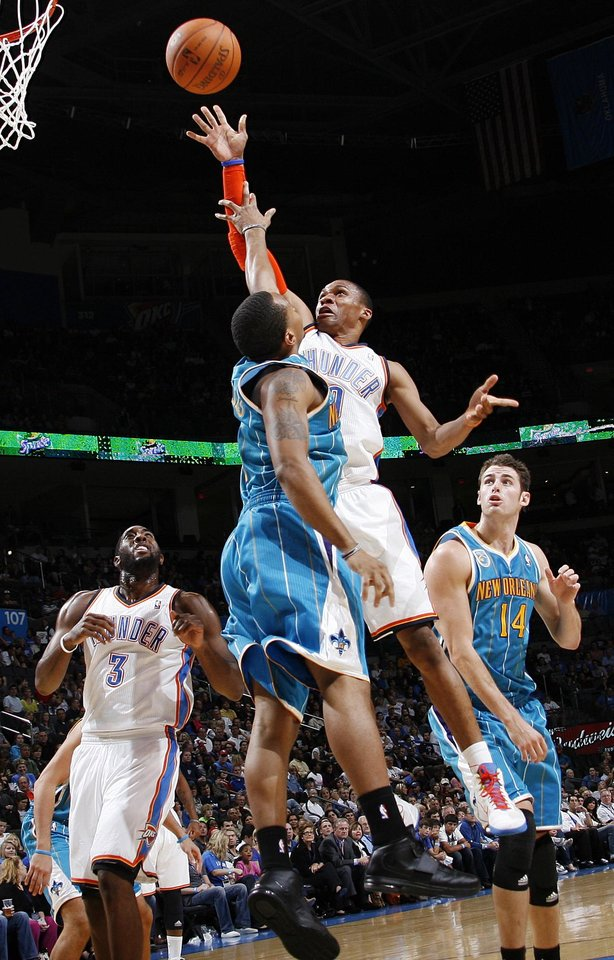 Photo - Oklahoma City's Russell Westbrook (0) shoots over Curtis Jerrells (0) of New Orleans between DJ White (3), left, of Oklahoma City, and Jason Smith (14) of New Orleans during the preseason NBA basketball game between the New Orleans Hornets and the Oklahoma City Thunder at the Ford Center in Oklahoma City, Thursday, October 21, 2010. Photo by Nate Billings, The Oklahoman