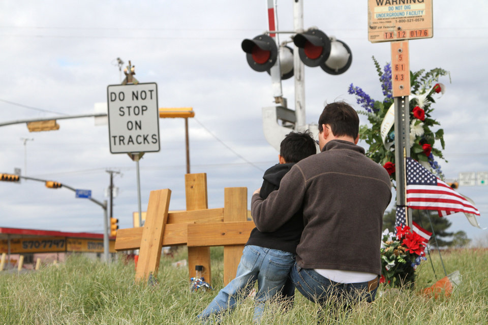 FILE - In this Nov. 18, 2012 file photo, Mark Thomas and his son Samuel deposit flowers at the site where a trailer that was carrying wounded veterans in a parade was struck by a train, in Midland, Texas. A 50-year-old Army veteran who served in Iraq and Afghanistan was driving the parade float that investigators say edged across a railroad crossing in Texas despite warning signals of a fast approaching train, the man's attorney said Tuesday, Nov. 20, 2012. Four veterans and sixteen people were injured in the resulting collision. (AP Photo/Juan Carlos Llorca, File)
