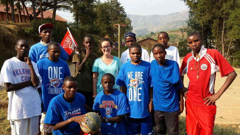 Betsy Dewey, a Peace Corps volunteer from Oklahoma City, is surrounded by her students in Rwanda. Dewey's father, Lyle, provided the Oklahoma City Thunder NBA basketball gear for the students on a trip to Africa last month. Photo provided