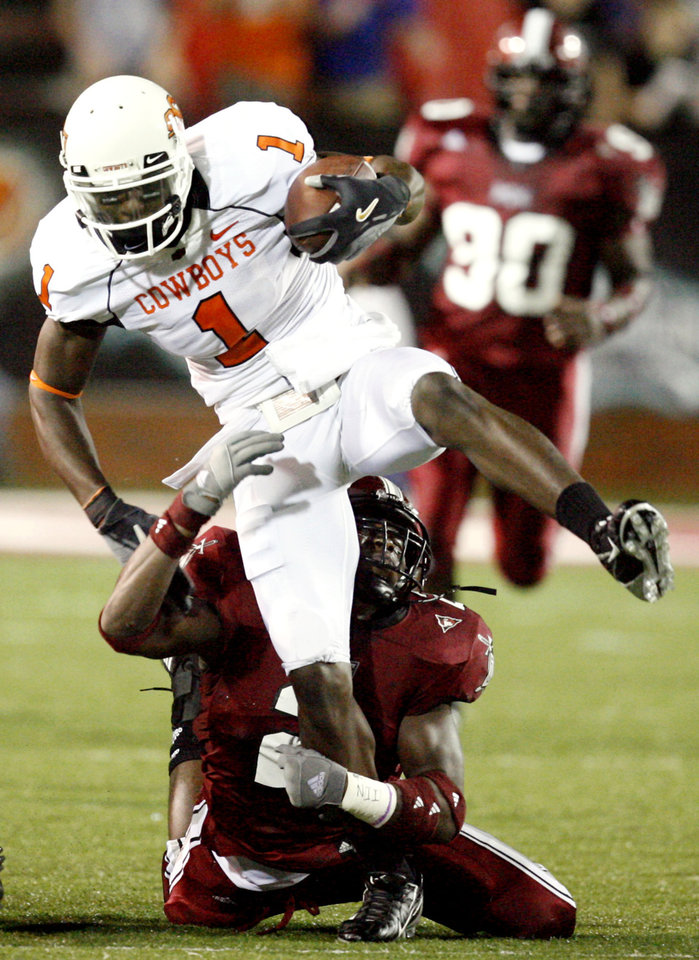 Photo - OSU's Dez Bryant (1) is taken down by Troy's Boris Lee in the first quarter during the college football game between the Troy University Trojans and the Oklahoma State University Cowboys at Movie Gallery Veterans Stadium in Troy, Ala., Friday, September 14, 2007. BY MATT STRASEN, THE OKLAHOMAN