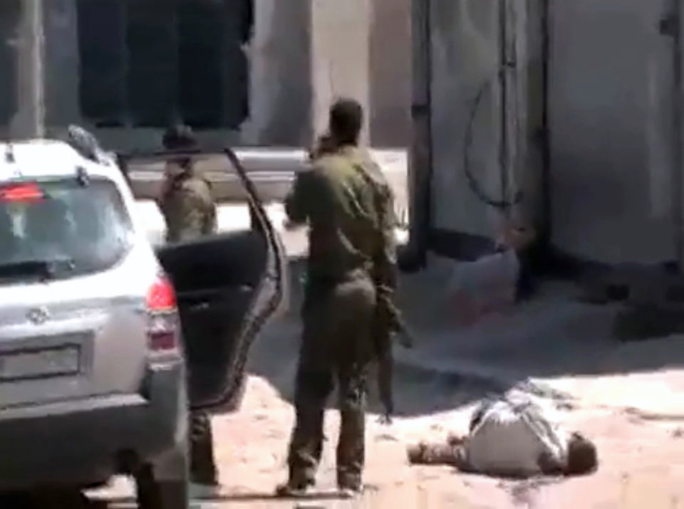 Photo -   This image made from amateur video and released by Syrian Media Centre Friday, April 13, 2012 purports to show a dead body next to Syrian soldiers in Daraa, Syria. (AP Photo/Douma Revolution in Syria via AP video) THE ASSOCIATED PRESS CANNOT INDEPENDENTLY VERIFY THE CONTENT, DATE, LOCATION OR AUTHENTICITY OF THIS MATERIAL. TV OUT