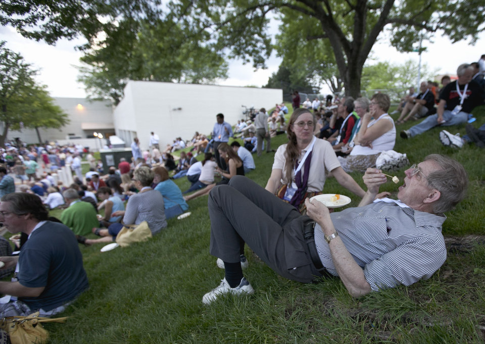 Photo -   Phil Martin of Minneapolis is watched by his wife Linda as he snacks with other shareholders outside the Berkshire-owned Borsheims jewelry store in Omaha, Neb., Friday, May 4, 2012. Berkshire Hathaway is expected to have 30,000 shareholders come to Omaha for it's annual shareholders meeting this weekend. (AP Photo/Nati Harnik)