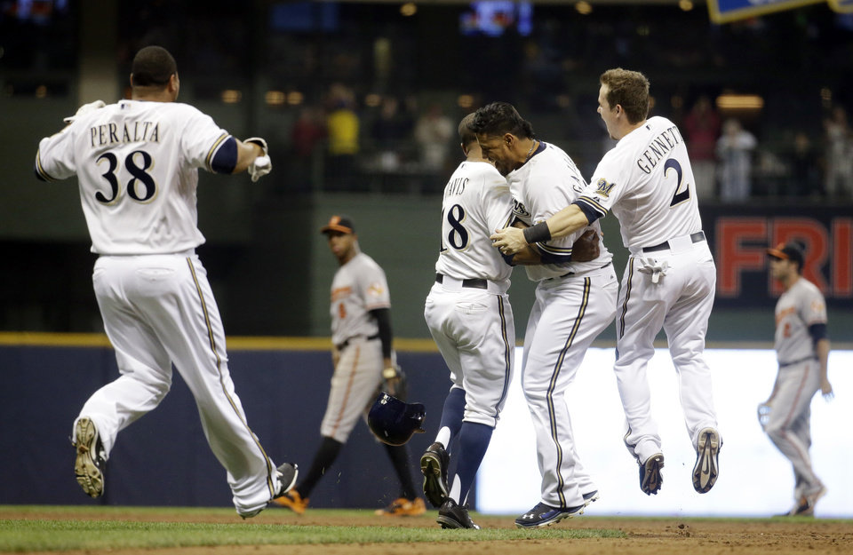 Photo - Milwaukee Brewers' Yovani Gallardo is mobbed by teammates 25after hitting a game-winning double during the 10th inning of a baseball game against the Baltimore Orioles Tuesday, May 27, 2014, in Milwaukee. The Brewers won 7-6. (AP Photo/Morry Gash)