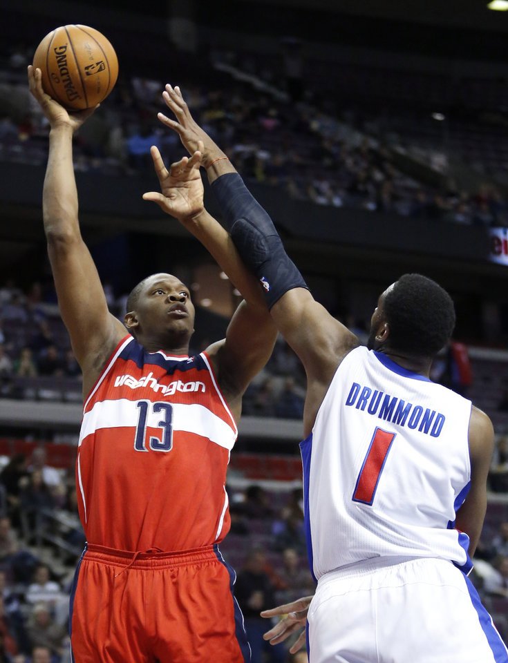 CORRECTS DATE - Washington Wizards center Kevin Seraphin (13) takes a shot against Detroit Pistons forward Andre Drummond (1) in the first half of an NBA basketball game in Auburn Hills, Mich., Friday, Dec. 21, 2012. (AP Photo/Duane Burleson)
