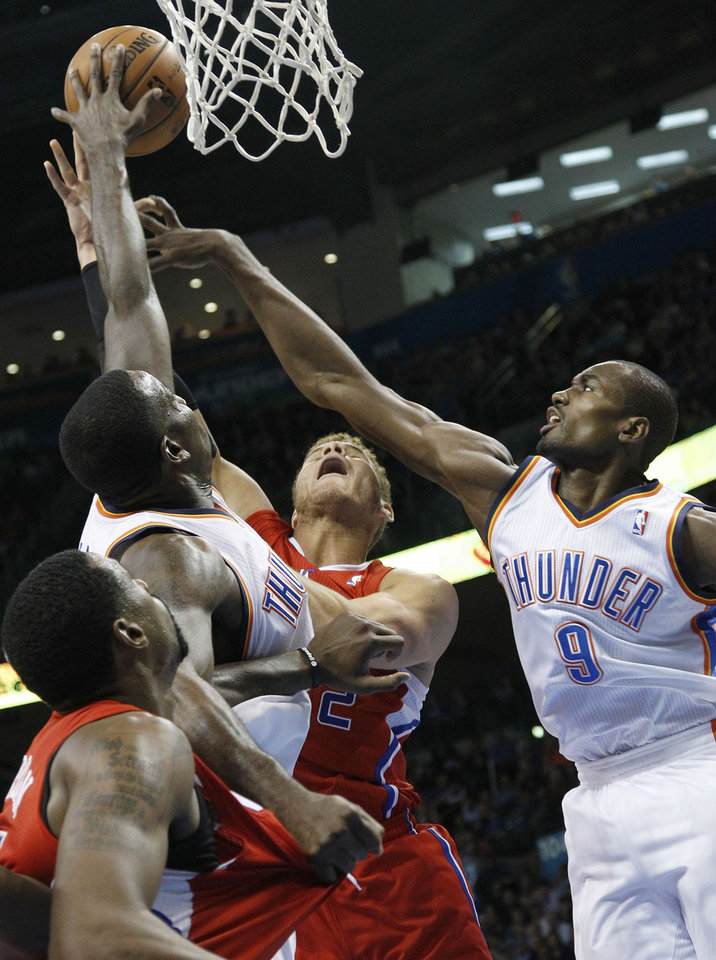 Photo -   Los Angeles Clippers forward Blake Griffin, center, has his shot blocked by Oklahoma City Thunder center Kendrick Perkins, left, as he is double-teamed by Perkins and forward Serge Ibaka (9) in the first quarter of an NBA basketball game in Oklahoma City, Wednesday, Nov. 21, 2012. (AP Photo/Sue Ogrocki)