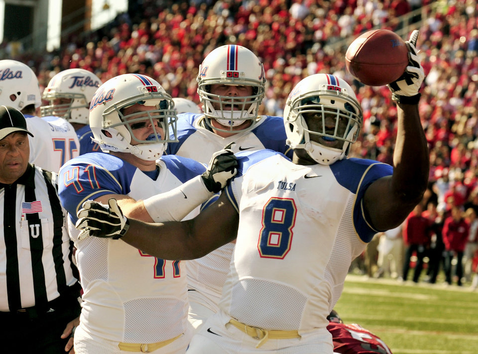 Tulsa running back Alex Singleton (8) celebrates his touchdown with teammates fullback Cody Wilson (41) and offensive tackle Jared Grigg, center, during the second quarter of an NCAA college football game against Arkansas in Fayetteville, Ark., Saturday, Nov. 3, 2012. (AP Photo/April L. Brown)
